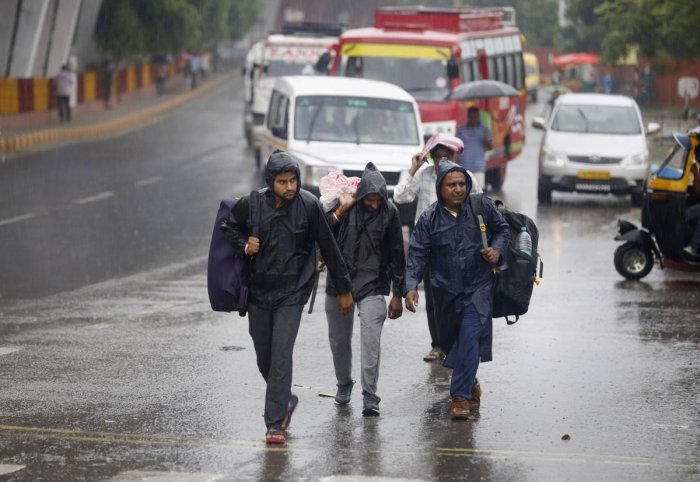 Pedestrians cross a road during heavy monsoon rainfall, in Jammu, Thursday, July 25, 2019. (PTI Photo)