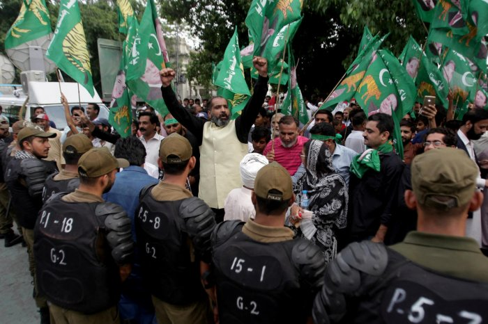 "Supporters of Pakistan Muslim League - Nawaz (PML-N) chant slogans as police officers block the road during a countrywide protest called ""Black Day"" against the government of prime minister Imran Khan, in Lahore, Pakistan July 25, 2019. (REUTERS)"