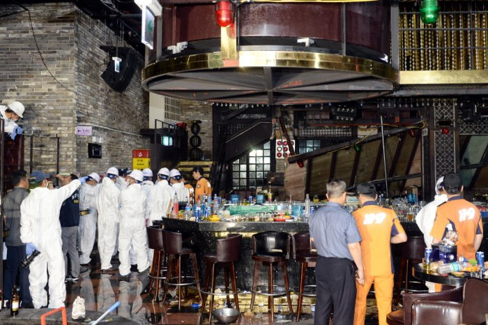 South Korean firefighters and officials examine the collapsed structure of a nightclub where several athletes competing at the World Aquatics Championships were dancing, in Gwangju (Reuters)
