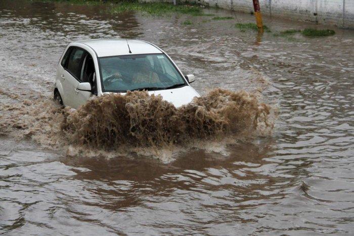 Vehicles ply on a waterlogged street following heavy monsoon rain in Jammu. Photo credit: PTI