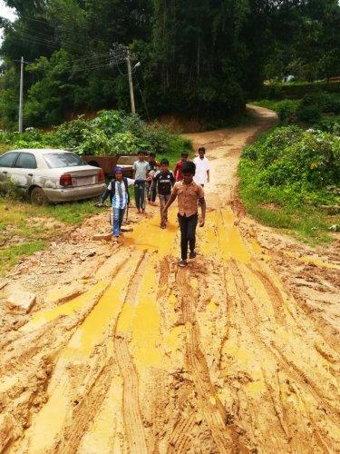 Children walk on the slush filled road leading to Gaddehalla Government Higher Primary School and Boys hostel near Suntikoppa.