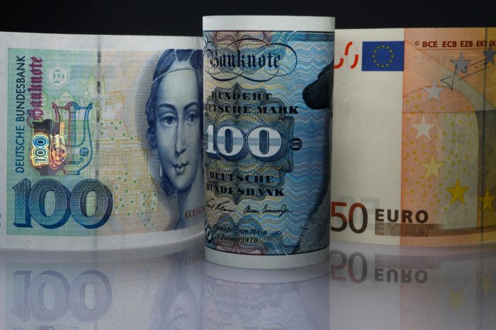 FILE PHOTO: One hundred Mark notes and fifty Euros note are seen in this photo illustration taken in Berlin on December 30, 2011. REUTERS/Pawel Kopczynski/File Photo