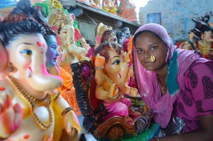 VIBRANT A woman of the Bawre tribe poses with idols of Lord Ganesha painted by them during Ganesh Chaturthi. PHOTOS BY AUTHOR