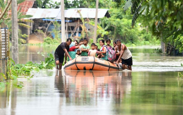 State Disaster Response Fund (SDRF) personnel rescue villagers on a boat from the flood-affected area of Jamguri village in Barpeta district of Assam. (Photo by Biju BORO / AFP)