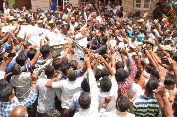 Villagers greet Chief Minister B S Yediyurappa at his native village Bukanaere in K R Pet taluk, Mandya, on Saturday.