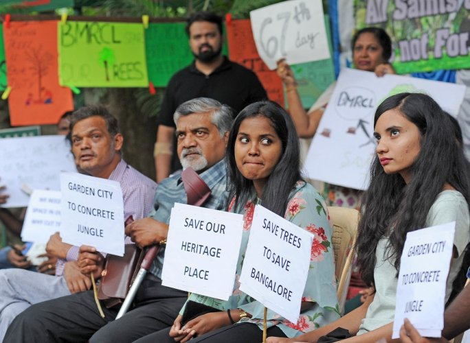 People staging a protest marking 67 days against BMRCL set to cut trees on the All Saints Church campus in Bengaluru. (DH Photo)
