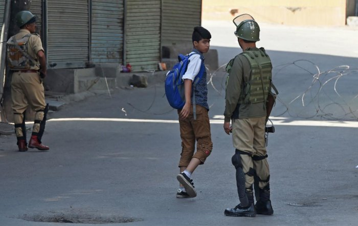 Security forces question a Kashmiri boy during the first day of a strike called by Kashmiri separatists against attempts to revoke articles 35A and 370 of the state constitution, in Srinagar. AFP