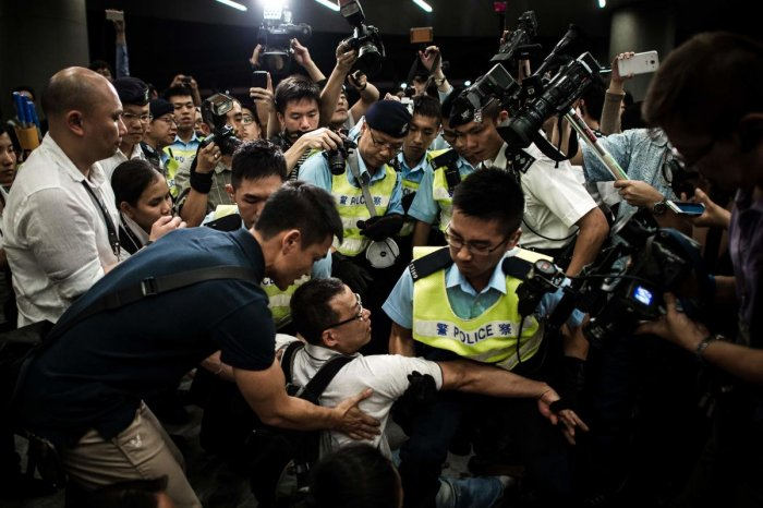 In this file photo taken on June 14, 2014, policemen remove protesters from the grounds of the Legislative Council in Hong Kong. AFP