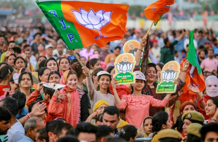 BJP supporters wave the party flag as they extend their support for Prime Minister Narendra Modi during a public rally ahead of Lok Sabha elections, at Dumi village near Jammu in March 2019. PTI File Photo