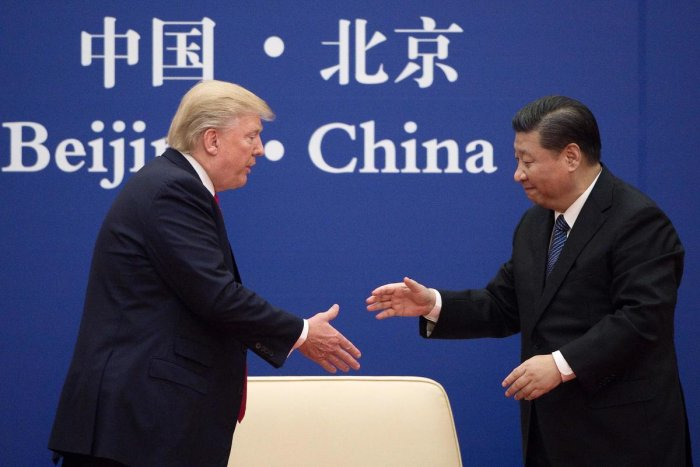 China's President Xi Jinping shakes hands with US President Donald Trump (L) during a business leaders event at the Great Hall of the People in Beijing in 2017 (AFP File Photo)