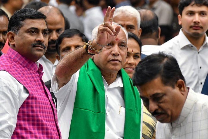 Senior leader of Bharatiya Janata Party (BJP), B.S. Yediyurappa (C), flashes the victory sign to his supporters and party workers prior to his swearing for the fourth time as the Karnataka Chief Minister. Photo credit: AFP