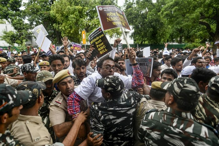 Police detain the doctors and students of Indian Medical Association (IMA) during a protest against the National Medical Commission Bill (NMC) outside Nirman Bhavan in New Delhi. (PTI Photo)
