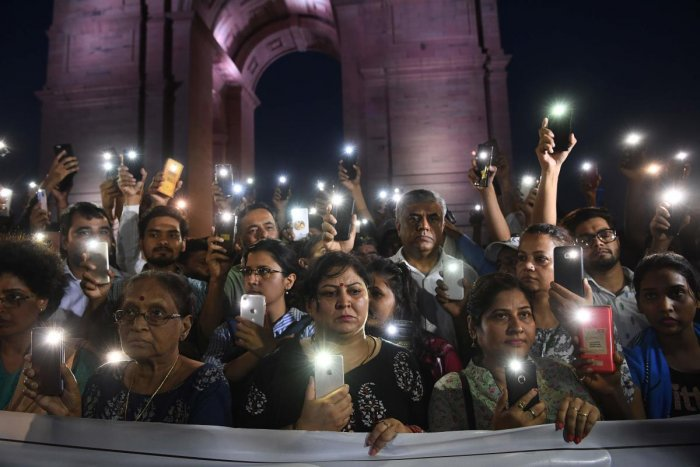 Indian social activists uses their mobile light as they take part in a solidarity rally in front of India Gate monument for the Unnao rape victim in New Delhi on July 29, 2019. ( AFP)