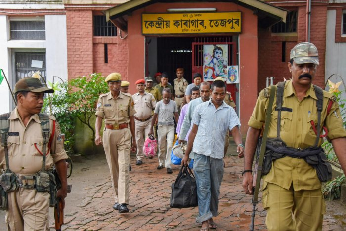 Four Bangladeshi nationals being escorted from the detention centre, at least 25 persons have died (PTI Photo)