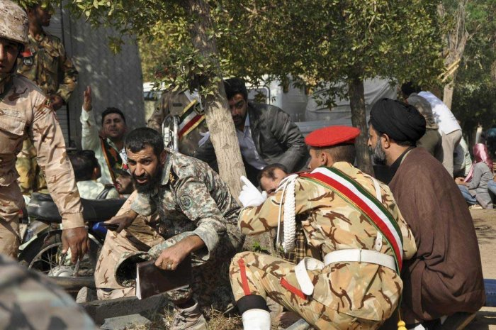 In this photo provided by the Iranian Students' News Agency, ISNA, Iranian armed forces members and civilians take shelter in a shooting during a military parade marking the 38th anniversary of Iraq's 1980 invasion of Iran, in the southwestern city of Ahvaz, Iran, Saturday, Sept. 22, 2018. Gunmen attacked the military parade, killing at least eight members of the elite Revolutionary Guard and wounding 20 others, state media said. AP/PTI