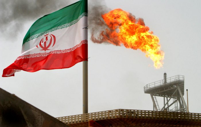 A gas flare on an oil production platform in the Soroush oil fields is seen alongside an Iranian flag in the Persian Gulf, Iran, July 25, 2005. REUTERS