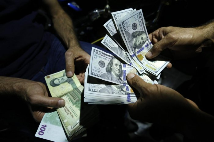 A man exchanges Iranian Rials against US Dollars at an exchange shop in the Iranian capital Tehran on August 8, 2018. AFP