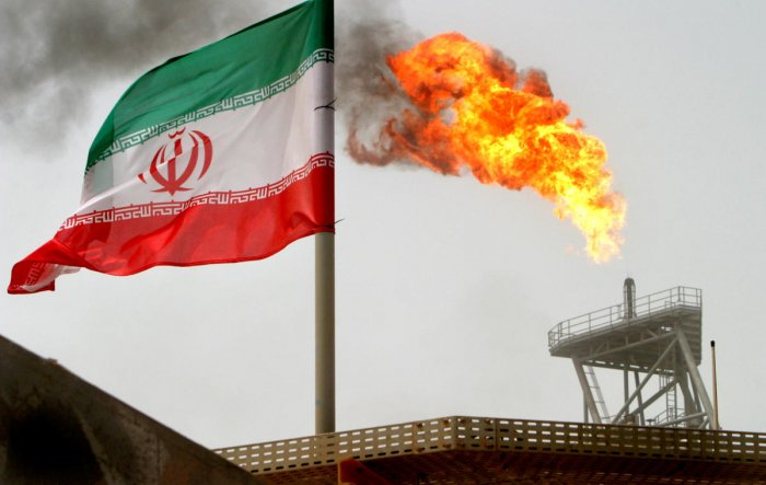 A gas flare on an oil production platform in the Soroush oil fields is seen alongside an Iranian flag in the Persian Gulf, Iran, in July, 2005. REUTERS