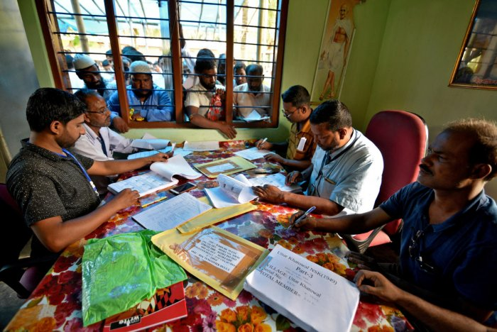 People wait to check their names on the draft list at the National Register of Citizens (NRC) centre at a village in Nagaon district, Assam state, India, July 30, 2018. (Photo by REUTERS)