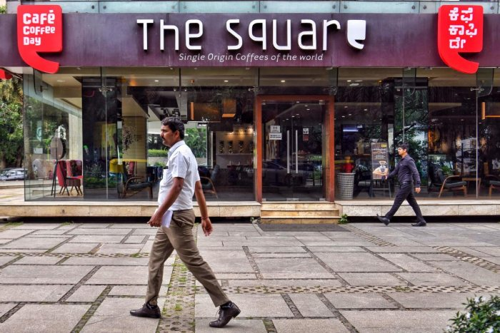 People walk past a closed outlet of Cafe Coffee Day retail chain belonging to coffee baron and founder V.G. Siddhartha in Bangalore on July 31, 2019. - The body of billionaire Indian coffee magnate V.G. Siddhartha was found by a river in southern India on