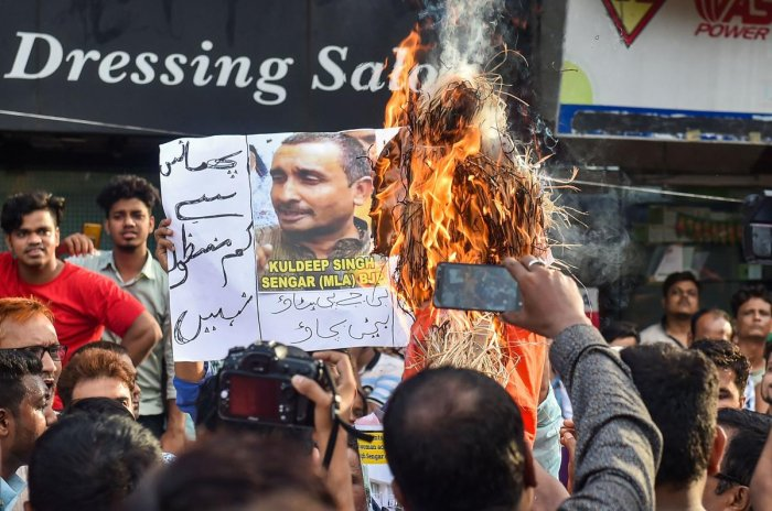 Youth Congress workers burn an effigy of UP Chief Minister Yoga Adityanath, as they display posters of main accused BJP MP Kuldeep Singh Sengar, near State BJP office in protest over Unnao rape incident in Kolkata. PTI photo