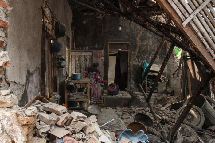 A villager looks for her belongings at her damaged house in Pandeglang, Banten province after a strong earthquake hit the area. (AFP Photo)