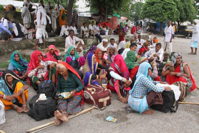 Tourists and passengers sit on the road as they prepare to leave at Jammu Railway Station in Jammu (PTI Photo)