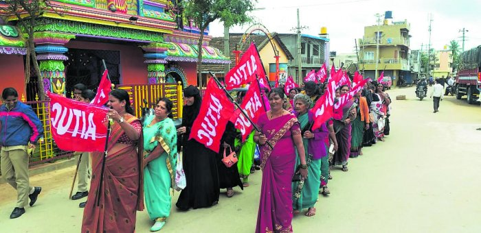 Akshara Dasoha workers take out a protest march in Chikkamagaluru on Saturday.