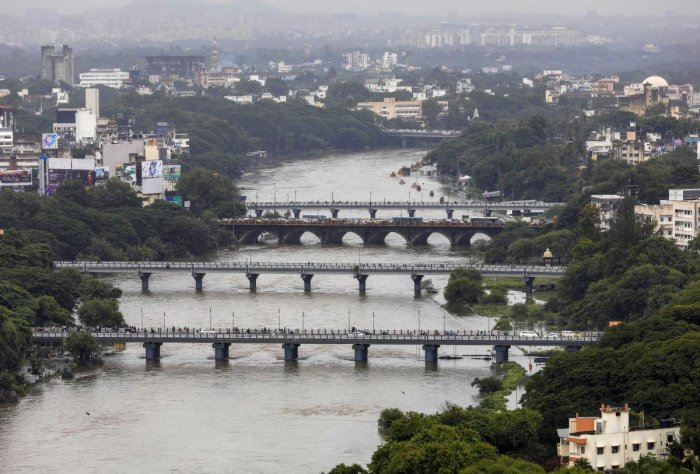 A view of the Mutha River flooded with rain and water released from Khadakwasla Dam, in Pune on Tuesday. PTI