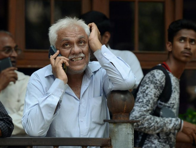 Investors watch movement of share prices on a digital broadcast outside the BSE in Mumbai. AFP FILE PHOTO