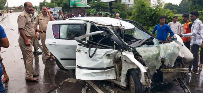 Police and people stand near the wreckage of the car in which the Unnao rape survivor was traveling during its collision with a truck near Raebareli. (PTI file photo)