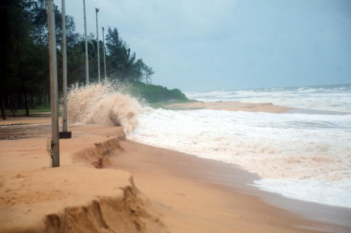 Electricity poles face the threat of being washed away due to sea erosion at Padubidri beach.