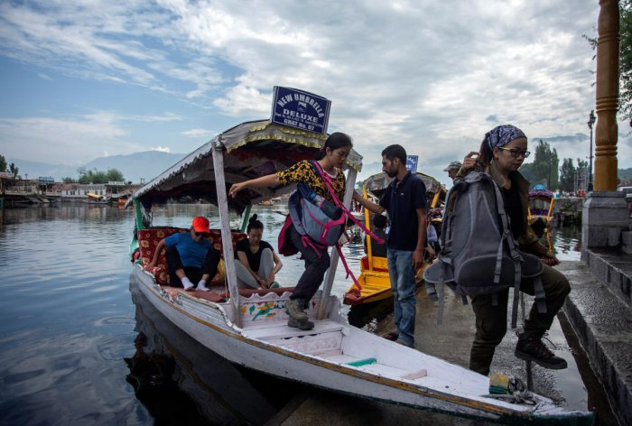 Foreign tourists disembark from a boat on the banks of Dal Lake as they prepare to leave Srinagar (Reuters Photo)