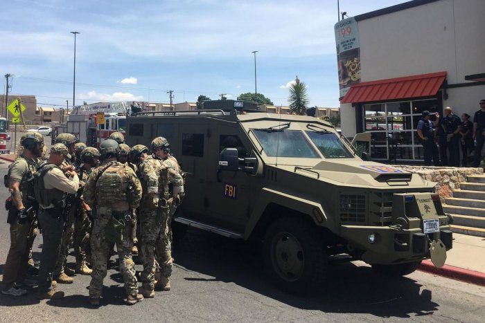 Armed Policemen gather next to an FBI armoured vehicle next to the Cielo Vista Mall as an active shooter situation is going inside the Mall in El Paso on August 03, 2019. AFP