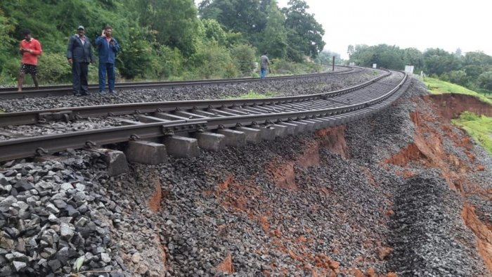 The soil bed beneath the rail tracks at Tinaighat section near Londa in Khanapur district of Belagavi is washed away due to heavy rain, affecting train movement. DH Photo