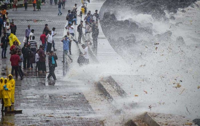Brihanmumbai Municipal Corporation (BMC) workers clear the garbage washed ashore during high tide, on the promenade along the Marine Drive, in Mumbai. (PTI Photo)