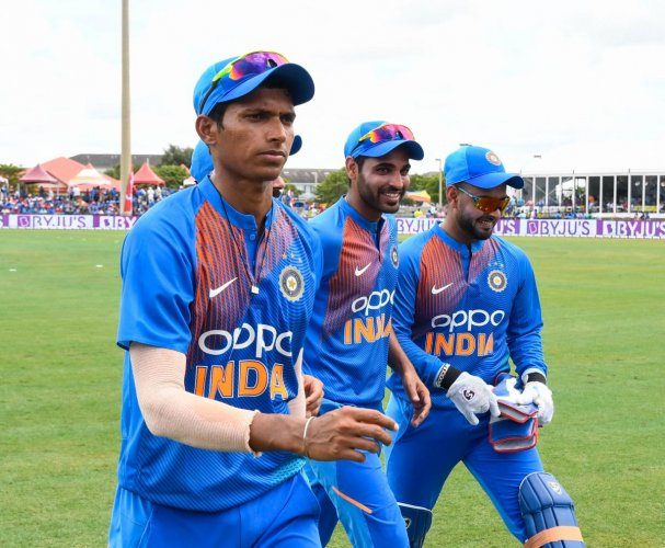 Navdeep Saini (L), Bhuvneshwar Kumar (C) and Rishabh Pant (R) of India walks off the field during the 1st T20i match between West Indies and India at Central Broward Regional Park Stadium in Fort Lauderdale, Florida, on August 3, 2019. (Photo by Randy Bro
