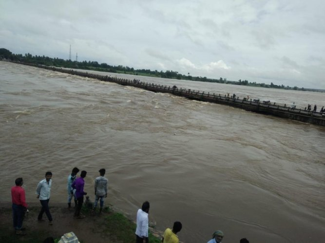 The Krishna river reaches the danger level at the Chikkapadasalagi Barrage in Jamkhandi taluk of Bagalkot district on Sunday. DH photo