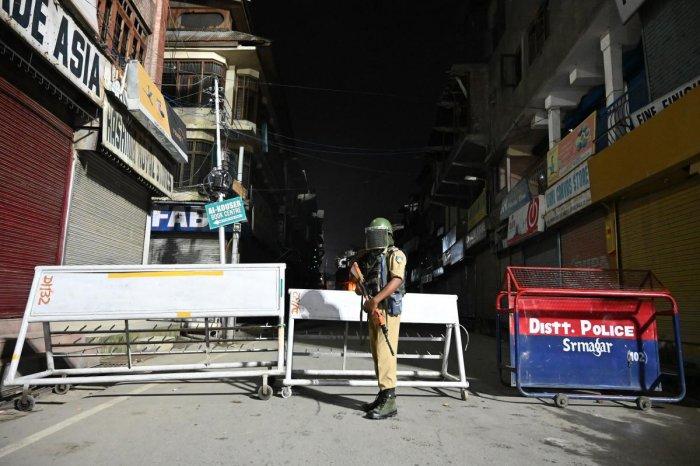 An Indian paramilitary trooper stands guard at a roadblock at Maisuma locality in Srinagar (AFP Photo)