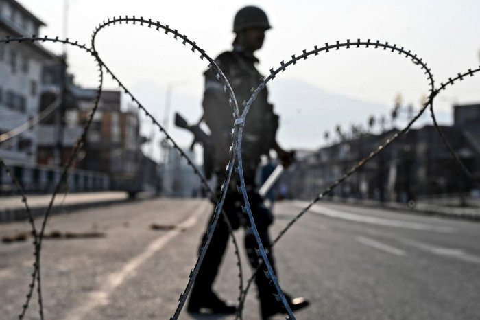An Indian paramilitary trooper stands guard on a road during a curfew in Srinagar. AFP photo