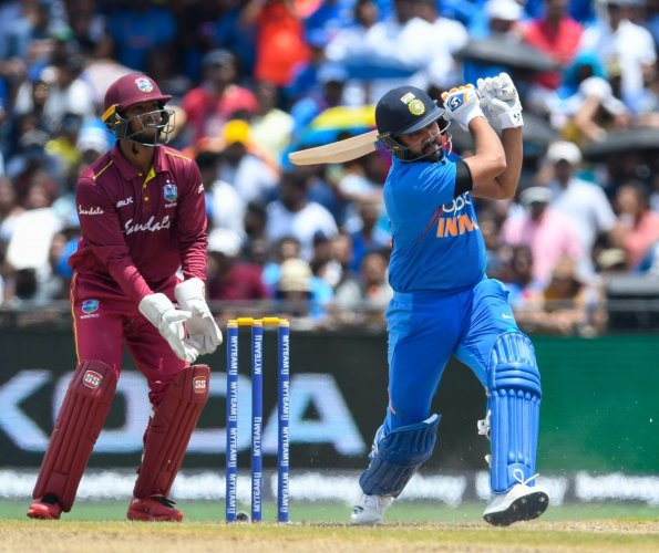 Rohit Sharma (R) of India hits 4 as Nicholas Pooran (L) of West Indies looks on during the 1st T20i match between West Indies and India at Central Broward Regional Park Stadium in Fort Lauderdale, Florida, on August 3, 2019. (Photo by Randy Brooks / AFP)