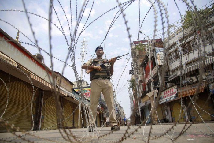 A CRPF man stand guard during restrictions at Raghunath Bazar in Jammu on Monday. Restrictions and night curfews were imposed in several districts as the Valley remained on edge. PTI