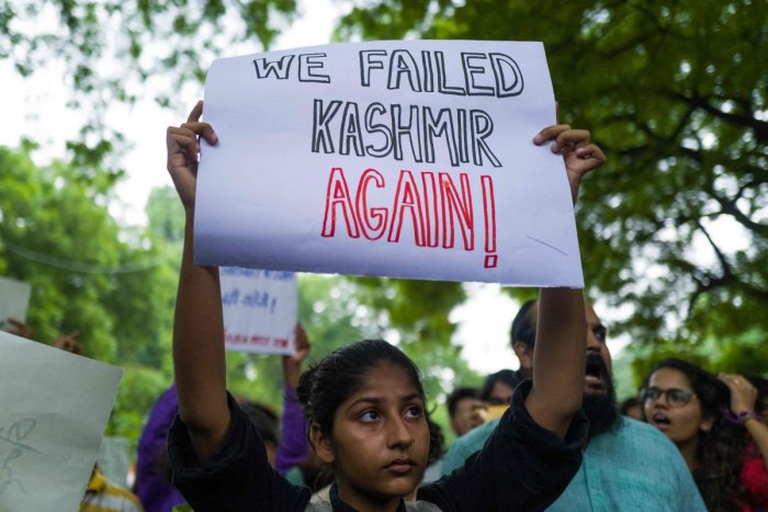 An activist and supporter of Indian left wing parties holds a placard during a demonstration to protest against the presidential decree abolishing Article 370 of the constitution giving special autonomy to Muslim-majority Kashmir, in New Delhi on August 5, 2019. - The Indian government on August 5 rushed through a presidential decree to scrap a special status for disputed Kashmir, hours after imposing a major security clampdown in the region. (AFP)