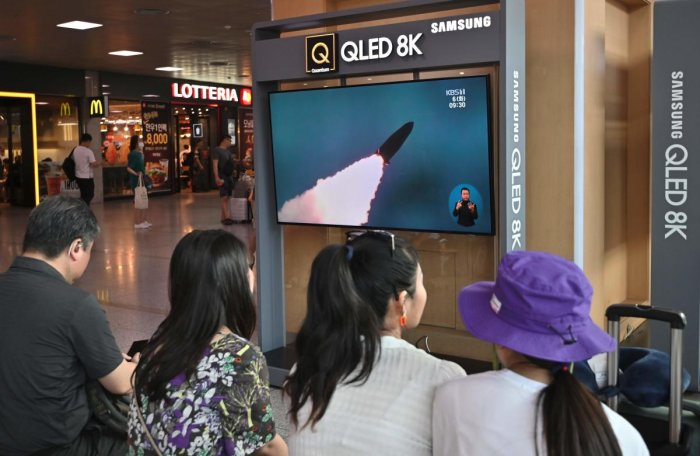 People watch a television news screen showing a file footage of North Korea's missile launch, at a railway station in Seoul (AFP Photo)