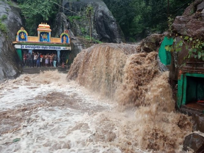 Tourists stranded inside Veerabhadreshwara Swamy Temple amid Kalhathagiri waterfalls in Tarikere taluk.