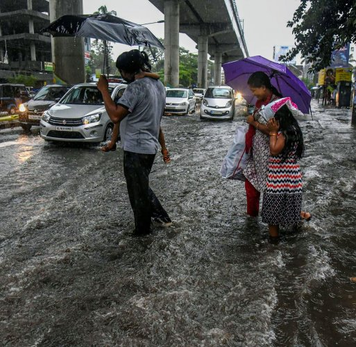 A family crosses a flooded road during Monsoon rains in Kochi (PTI Photo)