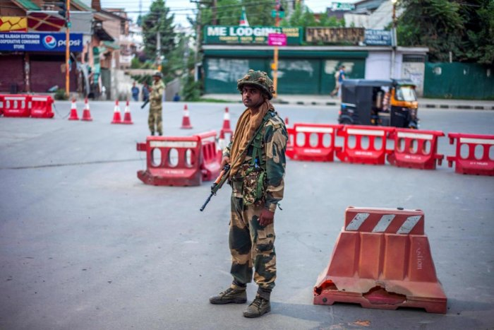 Security personnel stand guard on a street in Srinagar. (AFP Photo/Vikar Syed)