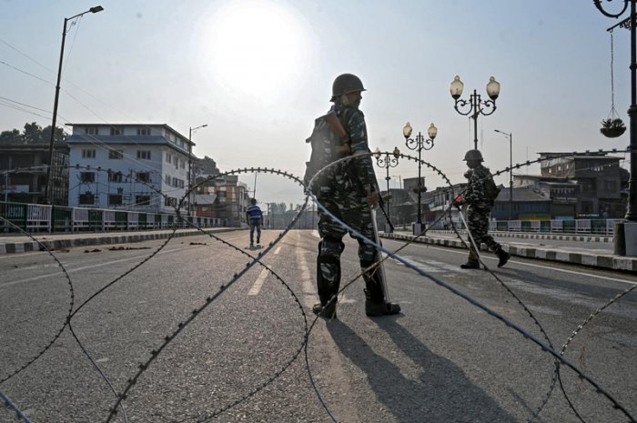 Paramilitary troopers stand guard behind a barbed fence wire as they block a road during a curfew in Srinagar. (AFP Photo)