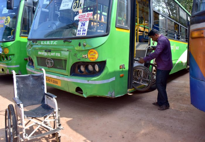 A person putting in side wheelchair in bus as a Assembly election at Police ground in Mangaluru on Wednesday. -Photo/ Govindraj Javali
