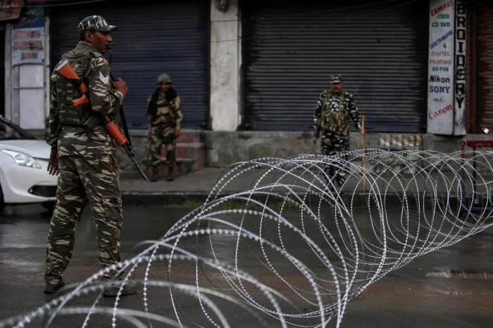 Security forces personnel stand guard next to concertina wire laid across a road during restrictions after the government scrapped special status for Kashmir, in Srinagar on August 7, 2019. REUTERS
